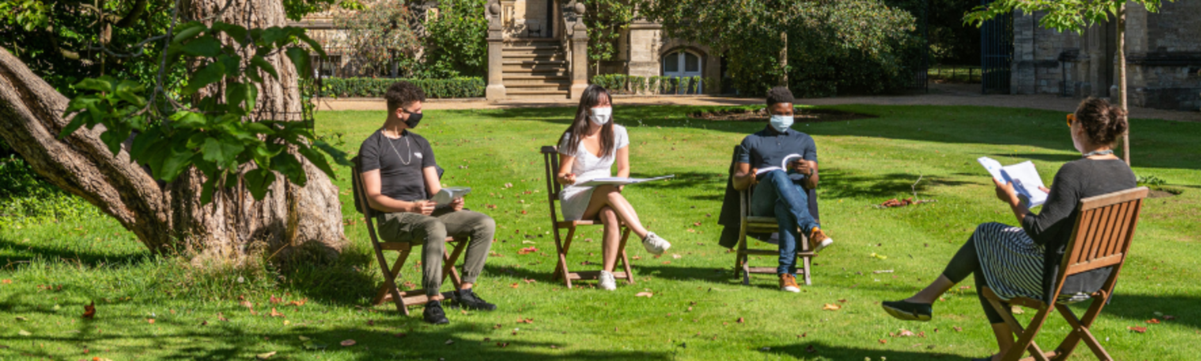 A tutor and 3 students of different ethnicity, all wearing face masks, sit distanced from one other on a college lawn, discussing their work