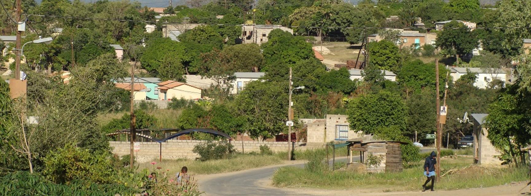 A scene of a rural south african town with overhead power cables and mountains in the background. A road runs through the middle.