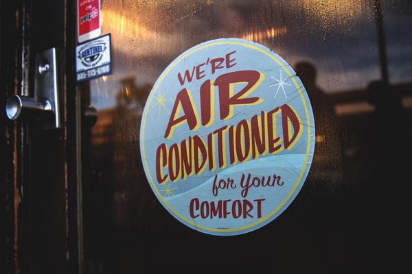 "A poster in a shop window reads ""We're air conditioned for your comfort"". The window is dripping in condensation, implying that it is hot and that air conditioning is necessary."
