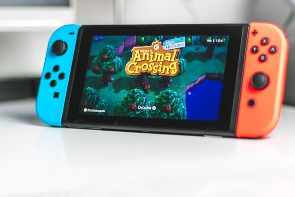 A video game device loaded with a game called 'Animal Crossing'