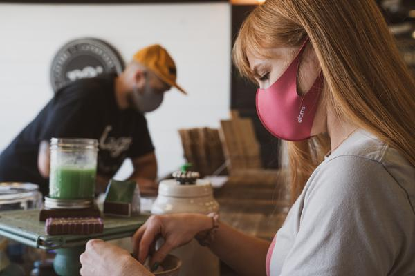 A man and woman, both wearing facemasks, are busy in a workshop