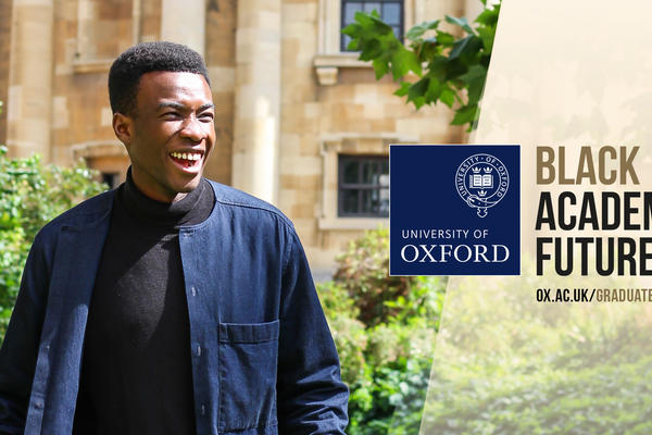 A Black postgraduate student outside an Oxford University building is smiling and laughing