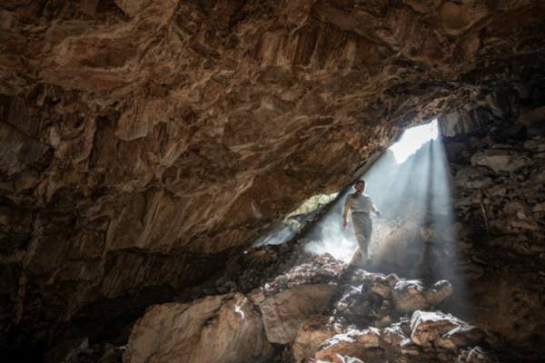 Dr Ciprian Ardelean inside Chiquihuite Cave, walking towards the archaeological excavations. It is very dark except for a ray of sunlight illuminating Dr Ardelean.