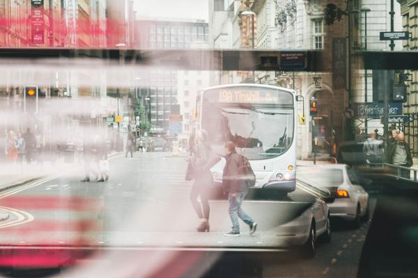 Photo of a bus window reflecting people walking and a bus and cars driving through a street. The image is slightly blurred and gives the impression of movement.