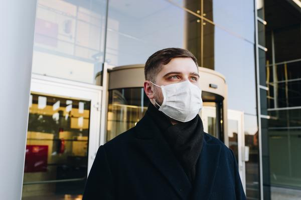 A man wearing a face mask, standing outside an office building in London