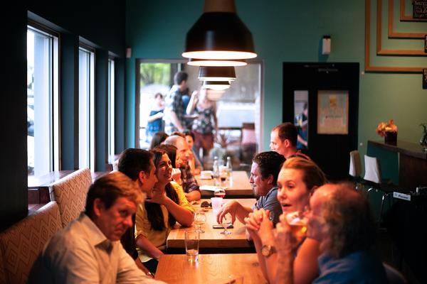 View from inside a pub restaurant, showing three tables surrounded by groups of friends smiling, laughing, talking, and enjoying drinks.