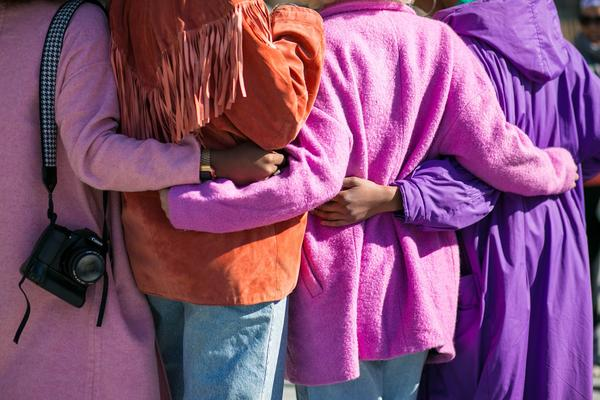 A diverse group of four women in brightly-coloured coats stand with their backs the camera and link their arms around each other's waists