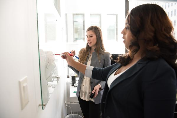 Two women of diverse ethnicities work together on a whiteboard using different coloured pens