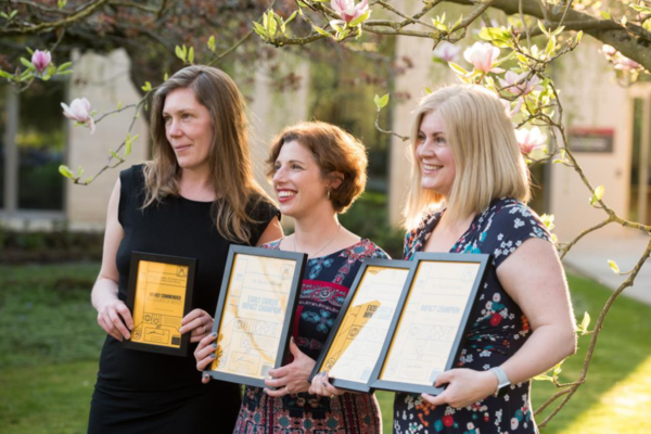 Three researchers stand in a sunny garden with a lawn and trees behind them, holding their prize certificates and smiling for the camera at the Excellence in Impact Awards