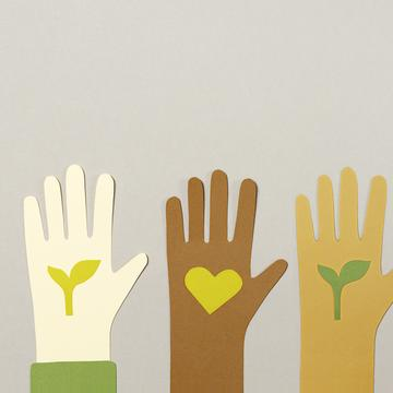 Three paper cut-outs of hands of different skin colour, each holding a paper cut out of a leaf or a heart