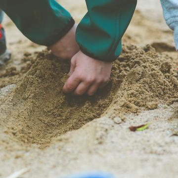 Shows a child's hands and feet as they crouch to dig a hole in the sand