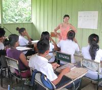 Professor Laura Rival smiles as she stands at the front of classroom, teaching a class of young adults. The classroom walls are bright green, the students and teacher are wearing clothes for hot weather, and out of the window a lush rainforest is visible.